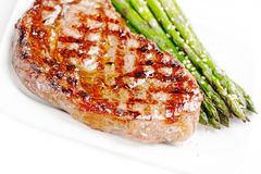 Barbecue grilled beef steak meat with asparagus. On white plate close up Royalty Free Stock Photos