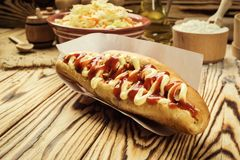 Barbecue Grilled Hot Dog with sauce,Hot Dog With Yellow Mustard,. Onion,Pickles and French Fries,Tasty hot-dogs with vegetables on wooden background, close up Stock Photography