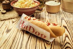 Barbecue Grilled Hot Dog with sauce,Hot Dog With Yellow Mustard,. Onion,Pickles and French Fries,Tasty hot-dogs with vegetables on wooden background, close up Royalty Free Stock Photo