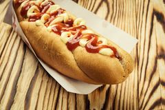 Barbecue Grilled Hot Dog with sauce,Hot Dog With Yellow Mustard,. Onion,Pickles and French Fries,Tasty hot-dogs with vegetables on wooden background, close up Royalty Free Stock Photography