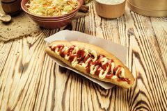 Barbecue Grilled Hot Dog with sauce,Hot Dog With Yellow Mustard,. Onion,Pickles and French Fries,Tasty hot-dogs with vegetables on wooden background, close up Stock Image