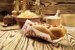Barbecue Grilled Hot Dog with sauce,Hot Dog With Yellow Mustard,. Onion,Pickles and French Fries,Tasty hot-dogs with vegetables on wooden background, close up Stock Photo