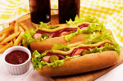 Barbecue grilled hot dogs, french fries and cola. On a kitchen board Stock Image