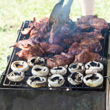 Barbecue grilled meat outdoor food meat and mushrooms on plate hands Stock Photos
