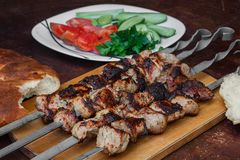 Grilled meat on skewers on a wooden tray, bread, vegetables and herbs around, on the table stock photo