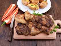 Barbecue grilled steaks. Chicken wings and baked potato Stock Photo