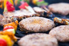 Barbecue with hamburgers and skewers Royalty Free Stock Images