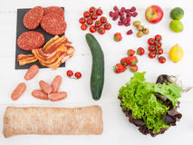 Barbecue ingredients on a white table top. An arrangment of barbecue ingredients with raw meat salad and fresh bread on a rustic white table top Stock Photography