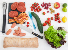 Barbecue ingredients on a white table top. An arrangment of barbecue ingredients with raw meat salad and fresh bread with utensils on a rustic white table top Stock Photos