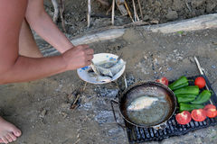 Barbecue on the island shore. After fishing. The fish rolled in cornmeal fried in the pan. Tomatoes and peppers are baked on hot grill stock photo