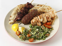 Barbecue kebab plate with tabouleh. Various barbecued kebabs - kofta, chicken tawook and sumac chicken - with tabouleh and pitta bread; an Arab or Lebanese-style Stock Photos