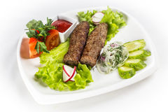 Barbecue kebab with vegetable. Kebab with vegetable and greens on white plate Stock Image