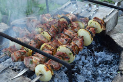 Barbecue marinated meat with onion and bacon. Shashlik or Shish kebab preparing on grill over charcoal in nature. Shashlyk skewere Stock Photography