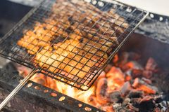 Barbecue meat cooking on fire - the ingredient of bun cha the famous Vietnamese noodle soup with bbq meat, spring roll, vermicelli stock photo