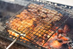 Barbecue meat cooking on fire - the ingredient of bun cha the famous Vietnamese noodle soup with bbq meat, spring roll, vermicelli. And fresh vegetable served royalty free stock images