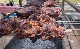 Barbecue meat roasted at spit for sale at city market. Barbecue meat roasted at spit for sale at farmers market stock photography