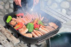 Barbecue with meat, sausages and peppers cooking on fire stock images