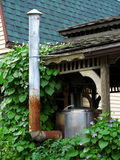Barbecue Meat Smoker. A barbecue meat smoker and chimney nestled in green vines on outdoor deck royalty free stock photos