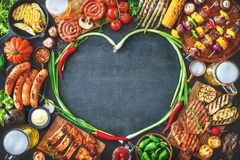Grilled meat and vegetables on rustic stone plate Stock Image