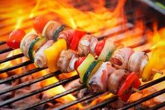 Barbecue met vlammen en plantaardig spit Stock Fotografie
