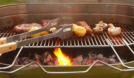 Barbecue met vlees, groenten en metaalbuigtang Royalty-vrije Stock Foto