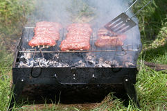 Barbecue with mici. Traditional Romanian barbecue raw meat (mici, mititei) on hot grill Stock Images
