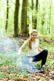 Barbecue in nature. Young girl preparing sausages on fire royalty free stock photos