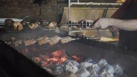 barbecue O assado posto de conserva é cozinhado em um soldador com batatas que seja envolvido na folha no carvão vegetal Batatas  vídeos de arquivo