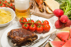 Barbecue party with beer, meat and vegetables Stock Images