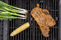 The Barbecue. A piece of Steak with scallions and corn Stock Photos