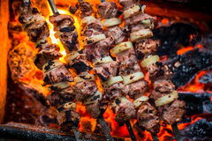 Barbecue pork kebabs on the hot grill close-up. Royalty Free Stock Image