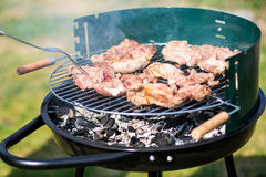 Barbecue pork meat cooking outdoors on a portable grill Royalty Free Stock Photography