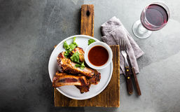 Barbecue pork ribs served on white plate with wine, top view stock image