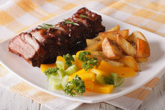 Barbecue pork ribs with a side dish of vegetables and fried pota Stock Photos