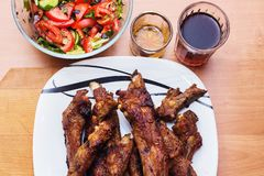 Barbecue pork ribs and vegetables on white plate, close up view stock photography