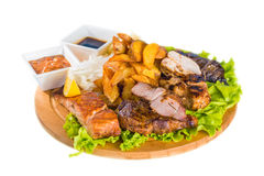 Barbecue pork, salmon steak, potatoes, salad and sauce Stock Image