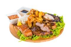 Barbecue pork, salmon steak, potatoes, salad and sauce Stock Image