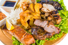 Barbecue pork, salmon steak, potatoes, salad and sauce Stock Photos