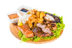 Barbecue pork, salmon steak, potatoes, salad and sauce Stock Photography