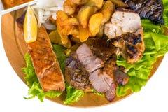Barbecue pork, salmon steak, potatoes, salad and sauce Stock Images