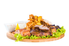 Barbecue pork, salmon steak, potatoes, salad and sauce Royalty Free Stock Photography