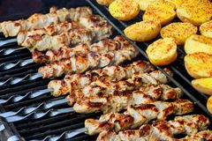 Barbecue skewers with potatoes and meat as well as kebabs are roasted on the grill. Barbecue potato skewers and meat as well as kebabs are roasted on the grill stock image