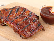 Barbecue Ribs. Barbecue spareribs with a bowl of sauce on a cutting board Royalty Free Stock Photo