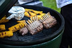 Barbecue ribs and corn on the grill. Spareribs on the grill. BBQ Grill With Pork Brisket And Corn Rings Royalty Free Stock Photography