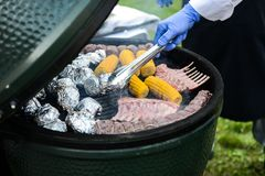 Barbecue ribs and corn on the grill. Spareribs on the grill. BBQ Grill With Pork Brisket And Corn Rings Royalty Free Stock Photos