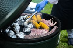 Barbecue ribs and corn on the grill. Spareribs on the grill. BBQ Grill With Pork Brisket And Corn Rings Stock Photos