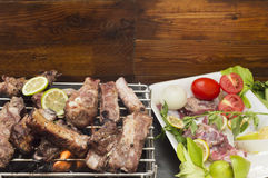 A barbecue. Roasted pork ribs on the barbecue and fresh ribs on the table Royalty Free Stock Images