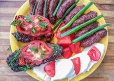 Barbecue roumain traditionnel de nourriture d'un plat jaune photos libres de droits