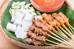 Barbecue satay served on traditional rattan plate with banana le Royalty Free Stock Photo