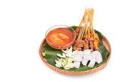 Barbecue satay served on traditional rattan plate with banana le. Freshly barbecue chicken and beef satay with gravy, rice, cucumber and onion served on Royalty Free Stock Photo